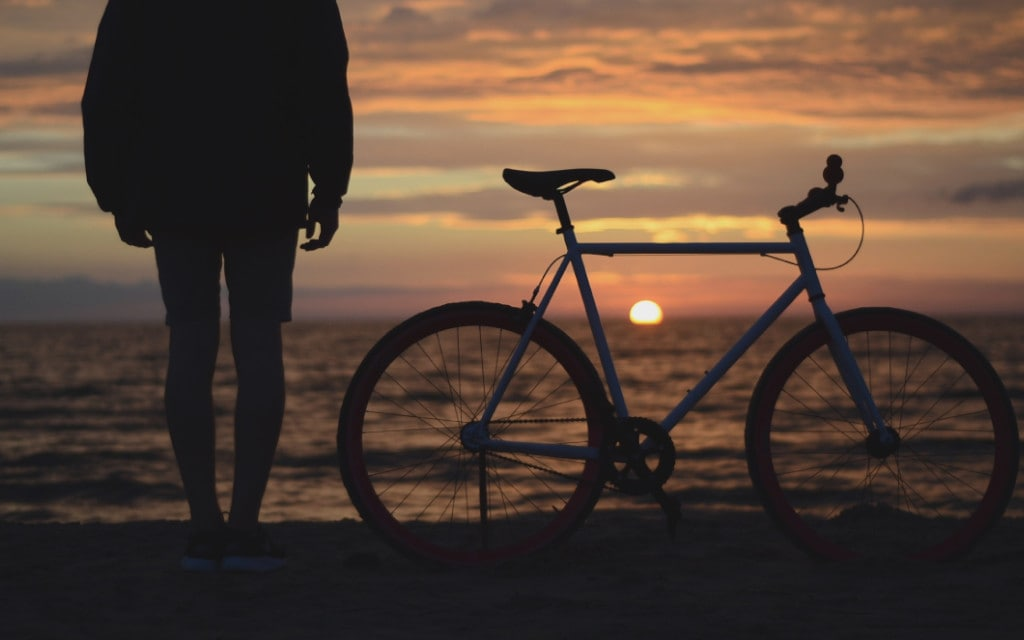 Man next to a bicycle  on the beach enjoying the sunset